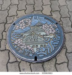 OSAKA, JAPAN - March 17, 2015: Art on the surface of Drain cap on the walk way…