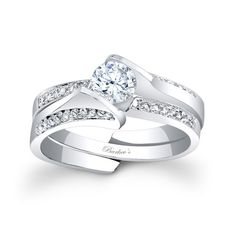 Diamond Bridal Set - 7884SW - Stunning and unique this interlocking diamond wedding set exudes confidence for the woman who wears it. Featuring a low profile cathedral shank engagement ring that rises to capture the channel set round diamond center securely in it's grasp, while pave set diamonds cascade down the shoulders. A pave set diamond wedding ring slips into the split open shank.   Also available in 18K and Platinum