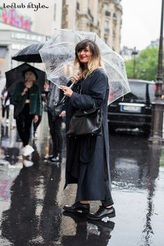 Womenswear Street Style by Ángel Robles. Fashion Photography from Paris Fashion Week. Woman under the rain in Paris wearing a black outfit with oversized dark blue coat.