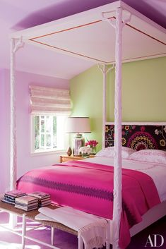 In the pink bedroom of a Beverly Hills home decorated by Peter Dunham, the hand-carved canopy bed is by Hollywood at Home; a vintage suzani covers the headboard, and the bedding is by Deborah Sharpe Linens.