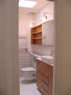 Baño juvenil realizado con encimera en silestone, mobiliario en roble, azulejos de 10x10 a rompejuntas, inodoro suspendido y un lucernario que permite la entrada de luz natural.