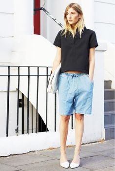A black collared crop shirt is worn with denim bermuda shorts, white pointed toe kitten heels and a white oversized clutch.