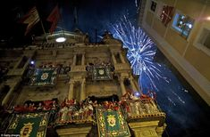 Revellers raise their scarves and candles as they sing the Pobre de Mi' song, marking the ...