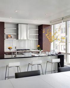 A cozinha é simples e de concepção básica com interligação ao ambiente de estar. Os armários da Bosch já estavam instalados quando a designer de interiores Barbara Littman comprou a cobertura. Da Ikea, os bancos altos dão um charme especial ao balcão que faz as vezes de mesa