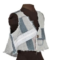 it's a boro-influenced vest, cropped, made from layers of linen, every square inch of which is stitched over in some way. Made from natural, white, and hand-dyed gray-blue linen, with stitching in white, khaki, grays, and maroon — with patches and tears and fraying, though none of it compromises the structure of it. Secret Lentil Clothing