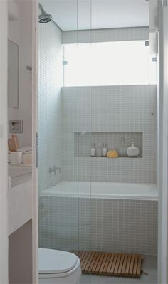 Narrow bathroom which has somehow squeezed in a walk in shower, and plunge bath; soft grey tiles and wood accents