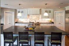 White kitchen with flat black countertops, black chairs, marble backsplash in NJ -  Knight Architects LLC