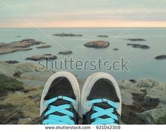Feet of the traveler on a rock above the sea with numerous stony islets. Sunset sky on the horizon. Sunset Sky, Stony, Boat Shoes, Photo Editing, Royalty Free Stock Photos, Sea, Rock, Sneakers, Norway