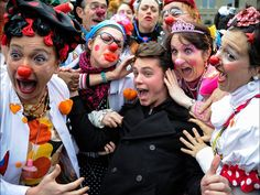 """Around 2OO """"Clown Doctors"""" or """"Giggle Doctors"""" of the children's care foundation Singer Bastian Baker, center, is surrounded by hospital clowns at the Federal Place on Jan. 30 in Bern, Switzerland. Clowns from around the world are attending a one-week seminar sponsored by the Theodora Foundation, a group dedicated to bringing smiles and laughter to hospitalized children through visits by clown doctors."""