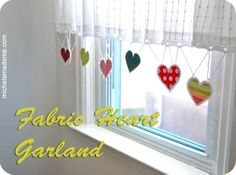hearts (bright colour with blanket stitch & corchet edges) hanging from curtain