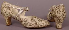 1920-1925  A pair of woman's ivory brocade pumps with woven leaf design in silver metallic thread. Silver leather straps fasten across the instep with rhinestone studded buckle