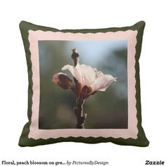 Pretty floral throw pillow with a blooming peach blossom, framed in pale pink, on a moss green background