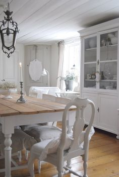 A white French farmhouse kitchen with natural wood floors and tabletop. So pretty!