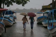 Residents walk past boats that were moved on land in preparation for the expected arrival of Hurricane Katia, in Tecolutla, Veracruz state, Mexico, Friday, Sept. 8, 2017. Hurricane Katia in the Gulf of Mexico is stationary north-northeast of Veracruz and forecasters didn't expect much movement overnight.