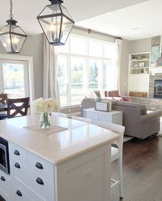 White farmhouse kitchen island with lantern pendants overlooking a craftsman lodge great room. Walls are Sherwin Williams Intellectual Gray with Alabaster trim.