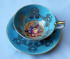 Antique aynsley tea cup set. Turquoise bone China tea cup and saucer. Turquise and gold tea set made in England. The fruit on the inside of the tea cup there is hand painted D. Jones. It is a pedestal tea cup. Beautiful item, highly collectible. Amazing pieces of very fine English