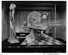 """Chromcraft dining room table, and chairs at The J.L. Hudson Company Department Store. Signage in the shape of the planet Saturn is affixed to the rear of the display and reads, """"Your Homemaking World, Past, Present, Trends,"""" A piece of butterfly print fabric hangs from the ceiling on the left side of the display, and features chrome cups, a clock, and bucket. The table is set at an angle, and features a chrome pitcher, cups and serving bowl"""