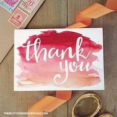 A red watercolor thank you card on a table with an envelope, ribbon, and scissors.