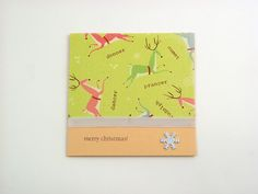 Christmas Reindeers - A classic Modern Opalescent folded card designed to add soft subtle highlight and warm richness. The card features a smooth peach coating with a high gloss finish on facing and reverse side. The design features decorative designer paper and a white satin ribbon detail runs through the front of the card. Finishing touch: metal snowflake. It comes with opalescent peach envelope in protective cellobag.