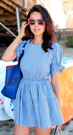 Annabelle Fleur is wearing a blue and white check gingham dress from Pixie Market and red sunglasses from Dolce Gabbana