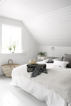 simple white attic bedroom with beadboard walls and ceiling