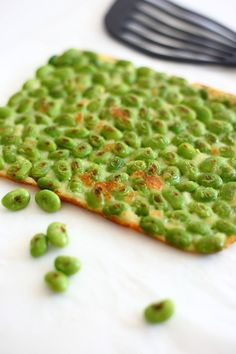 I believe this is edamame pressed into a cracker dough recipe & baked in oven ( recipe in Japanese- no translator)