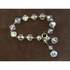 """Sparkling vintage aurora borealis multi faceted round glass beads in hues of blues, pinks and purples are linked together with silver tone metal and two dangling multi faceted graduated aurora borealis glass bead strands dangle below the clasp. Ultra feminine bracelet matches nearly everything and works day or night. This bracelet is comprised of ten 1/2"""" beads with two smaller 3/8"""" in diameter beads at the clasp end which allows the bracelet to close easily at the spring ring clasp closure…"""