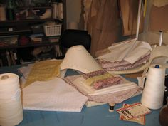 A stack of work dresses to be put together by Thomas, and a bonnet ready to cover  -who will get to it first?