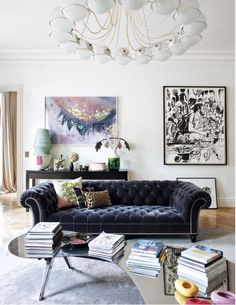 Room Decor Ideas: a white wall living room that is complete by two paintings Tha black sofa with printed pillows looks so confortable with the coffee table full of books