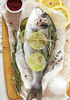 10 Most Misleading Foods That We Imagined Were Being Nutritious! Fresh Sea Bream With Lemon, Lime, Rosemary, Salt And Pink Pepper On Wooden Cutting Board And Paper Wrapping. Raw Food Recipes, Fish Recipes, Seafood Recipes, Gourmet Recipes, Food Styling, Food Photography Styling, Fish Dishes, Seafood Dishes, Cuisine Diverse