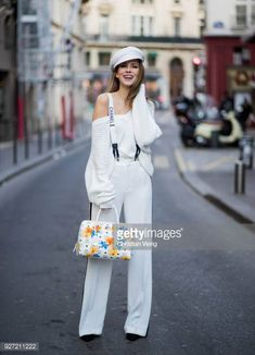 Alexandra Lapp wearing white sport pants with stripes on the side and a white knit v neck pullover from Zara a white Baker Boy Cap from Chanel...
