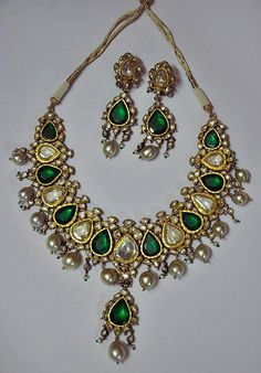 A Suite of Indian Polki Diamonds, Emeralds and Pearl Jewellery, comprising a necklace of closely connected pan shaped emeralds and polkis, un-cut diamonds set in kundan (24 cts gold), surrounded by polkis, suspending a fringe or similar pear shaped plaque with south sea pearls, with a pair of matching earrings