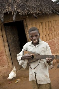 Chibeza Oscar Kalusa, whose family participated in the Mika Village Draft Cattle Project in Zambia, plays a ukulele outside his home.