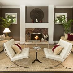 a great example of how repeated lines (round plate and curved legs on Barcelona chairs); (square fireplace mantle, square pictures) enhance a room.  Also the tone-on-tone colors.  Love it!