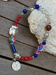 Funky sterling silver charm bracelet featuring millefiori Venetian beads, red coral and lapis lazuli by MuranoBling on Etsy https://www.etsy.com/au/listing/507314229/funky-sterling-silver-charm-bracelet