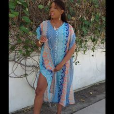 """Beach Cover Up/Kaftan This gorgeous kaftan style cover up is perfect for your next tropical getaway. Feel completely covered in this longer style cover up. Lightweight and packable polyester. Ever so slightly sheer. Since it is retail, it has no tags, but comes to you in its original sealed packaging. Measures 50"""" from top of shoulder to bottom. Laying flat, measures 25"""" armpit to armpit. 12"""" wide arm hole. My model is 5'9"""", and measures 41"""" bust, 32"""" waist, 41"""" hips. Swim Coverups"""