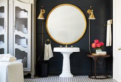Chic bathroom with brass sconces, a large round mirror over a pedestal sink - a French armoire and black walls