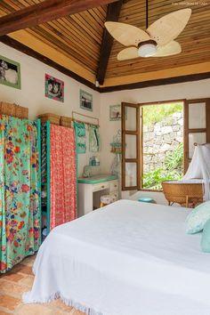 As estantes de madeira receberam pintura na cor verde e cangas estampadas foram usadas como cortina para o armário.