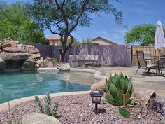 This landscape features a fire pit, barbecue, flagstone deck and pool with waterfall perfect for the weekend in Desert Ridge in Phoenix, AZ - www.lonestaraz.com