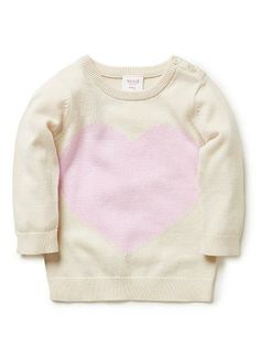 100% Cotton Jumper. Fully fashioned knit, long sleeve jumper. Features oversized heart intarsia on front. Crew neck, with 3 button opening on left shoulder. Available in Cake.