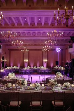 Elegant ballroom, wedding reception, floral arrangements, indoor wedding, high ceilings, dim lighting, purple lighting