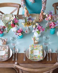 """Pretty Tablescape Inspired by Calico. Liberty of London fabrics were used to create the napkins at each place setting (have a tailor or handy friend cut and hem them to 20-inch squares), and it inspired the flowers on the table. Several Middle Kingdom """"Red Chamber series"""" vases -- overflowing with wildflowers, daisies, ranunculus, pink nerines, purple clematis, clover foliage, and muscari -- run the length of the table (globaltable.com). Let each guest take one home as a favor."""