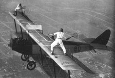 Two men play tennis on the wings of a bi-plane, c.1920