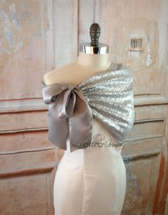 Gorgeous silver sequin shrug with a beautiful double faced satin self-tie closure. This pretty sequin shawl can be worn as a shrug, bolero, shoulder wrap, caplet, or stole. Shown here in silver. Also available in ivory, black, white, gold or blush. For color chart, please visit our website http://lucilleandirma.com/products/ivory-sequin-shawl-shrug These are lined with a luxurious 4 way stretch fabric. Sizes As Follows: XS/S US Sizes 2-6 M US Sizes 8-10 L US Sizes 12-16 XL US Sizes 18-20…