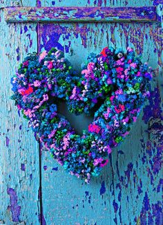 Beautiful small colorful floral heart wreath on a wonderful shabby chic blue door