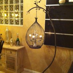 A Vintage bird cage, as a standing lamp next to the couch.