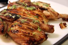 """Scallion and Lime Butter """"Brick Grilled"""" Chicken with whole roaster chicken, butter, oregano, cumin, salt, pepper, scallions, and lime juice. Photo tutorial graphically shows how to cut chicken apart to get it to lay flat on grill. Chicken is rubbed with herbs then put on grill. Bricks are wrapped in foil and layed on top, 10 minutes each side. When fully cooked, scallion lime butter is melted on top. Slice and serve, makes 4-6 servings. This is the perfect recipe for a Traeger Grill!"""
