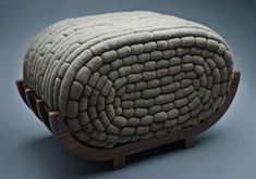 Rack and Roll by Monomoka: pale gray roll of 843 crocheted linen cocoons form the seat on a base of 4 walnut arches.