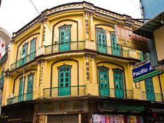 Yellow corner building with balconies and green doors, Macau