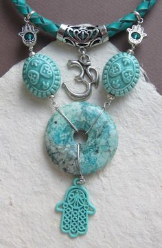 This necklace combines protective Hamsa-amulet pendant, also known as Fatima Hand, OM mantra pendant, accompanied with turquoise donut, glazed porcelain beads and handbraided leather cord.  Hamsa can protect you against the evil eye and from various failures and OM mantra will give attitude to succeed.  Necklace length 42,5 cm (17), turquoise donut 4 cm (1 1 2)  This item will arrive to you in a pretty safe cardboard box. Ill ship your order within 1-3 business days, and youll receive a…